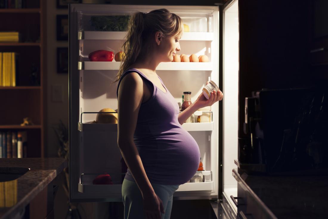 Femme enceinte à la recherche dans le réfrigérateur la nuit.