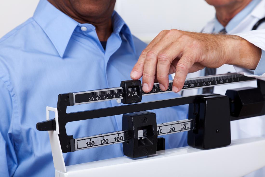 Homem na escala de pesagem com o médico.