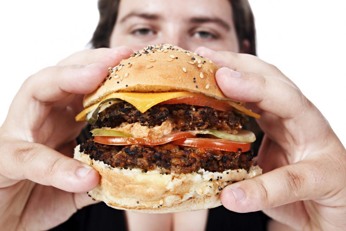 uomo con hamburger malsano