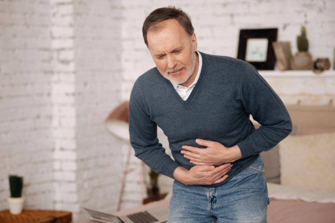 男はIBSに苦しんで、胃を抱えながら痛みを抱きました。
