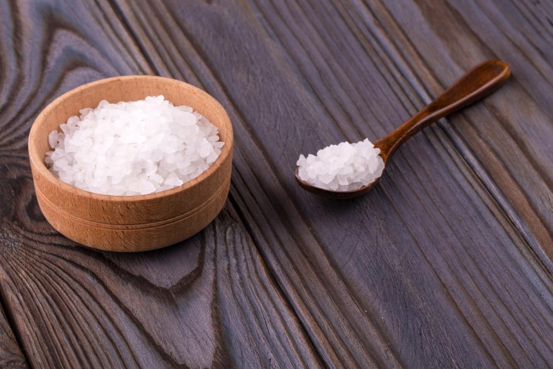 木製のボウルとスプーンはエプソム塩で満たされ、木製のテーブルに置かれています。