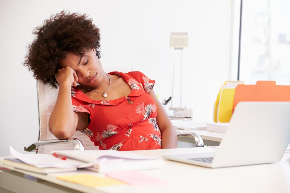 [donna stanca al lavoro che riposa la testa in mano]