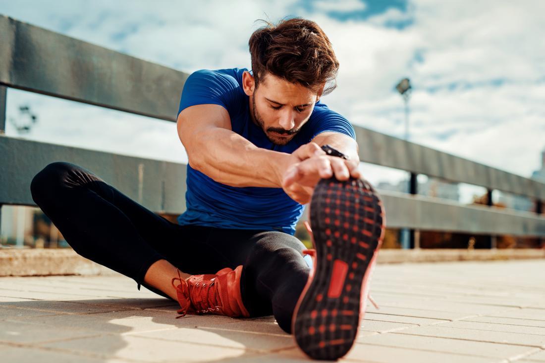 Човек, който седи, разтягайки краката си и хамутките, преди да се упражнява.