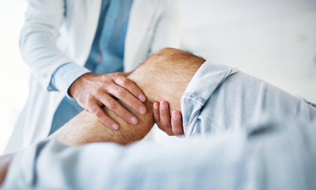 Schmerzen hinter dem Knie des Patienten auf dem Untersuchungstisch, der vom Physiotherapeuten überprüft wird.