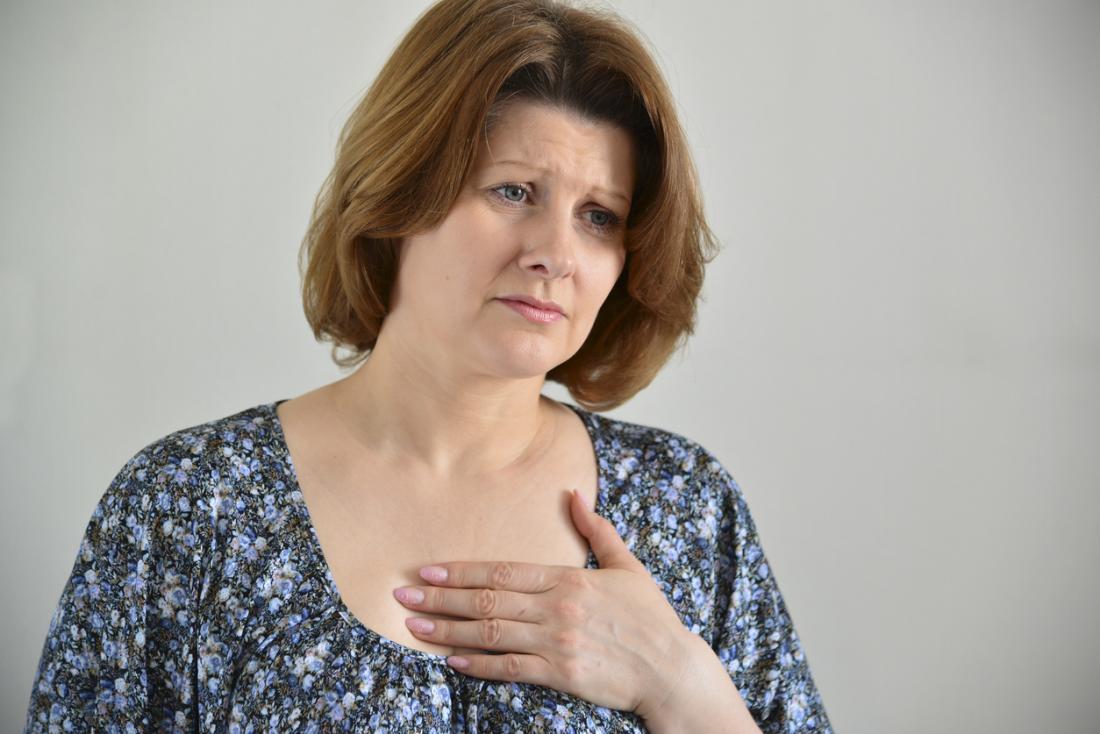 Femme tenant son sternum à cause de la douleur.