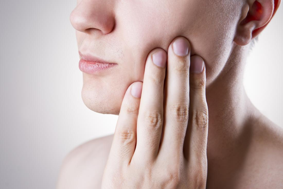 Femme avec péricoronitis frottant la joue mal de dent de sagesse.