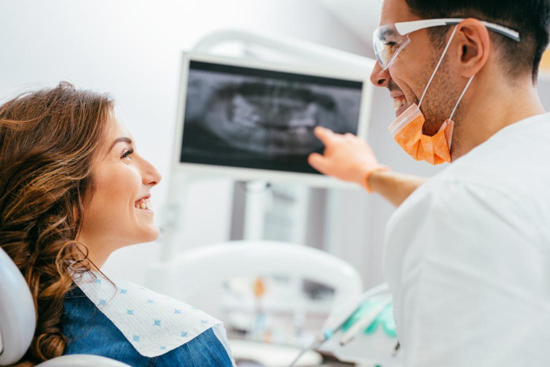 Femme chez les dentistes en regardant une radiographie de ses dents.