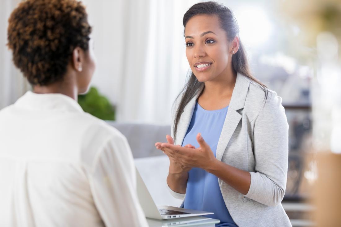 Femme médecin parlant à une patiente dans un bureau moderne propre.