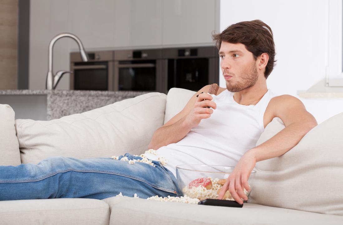 homem entediado comendo no sofá