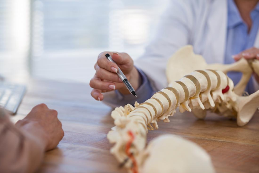 Доктор обяснява Spina bifida occulta като посочва модел на човешки гръбнак.