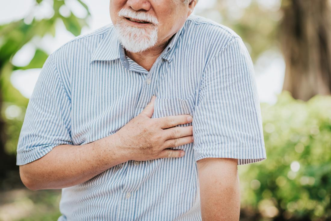 Senior homme tenant sa poitrine à cause de la douleur cardiaque