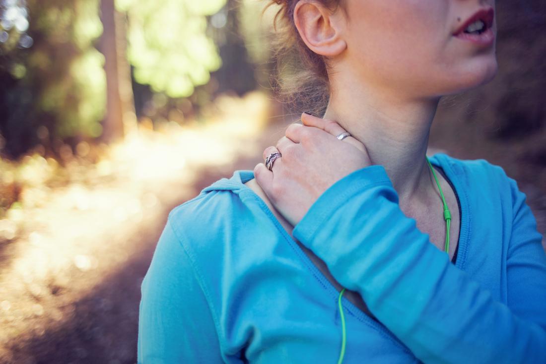 外に走っている間に襟と肩をつかむ肩甲骨関節の傷害を持つ女性。