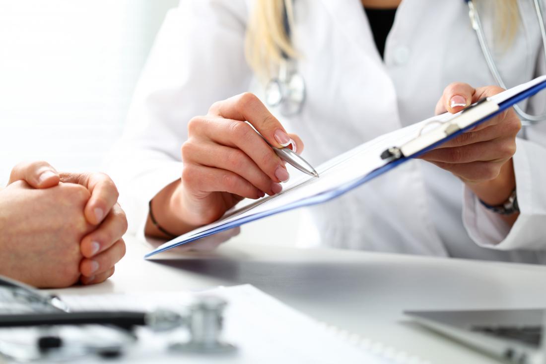 医者は結果を議論するために患者にそれを示すクリップボードを持っています。
