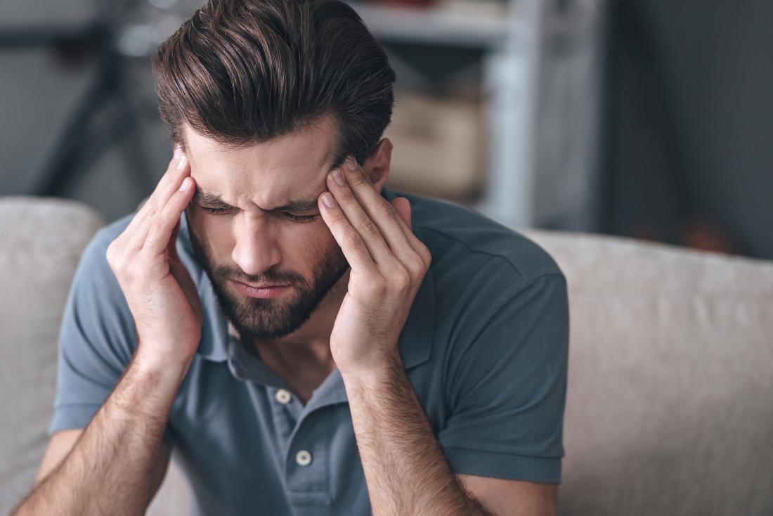 Човек с мигренозно главоболие, който масажира слепоочията си и се намръщи.