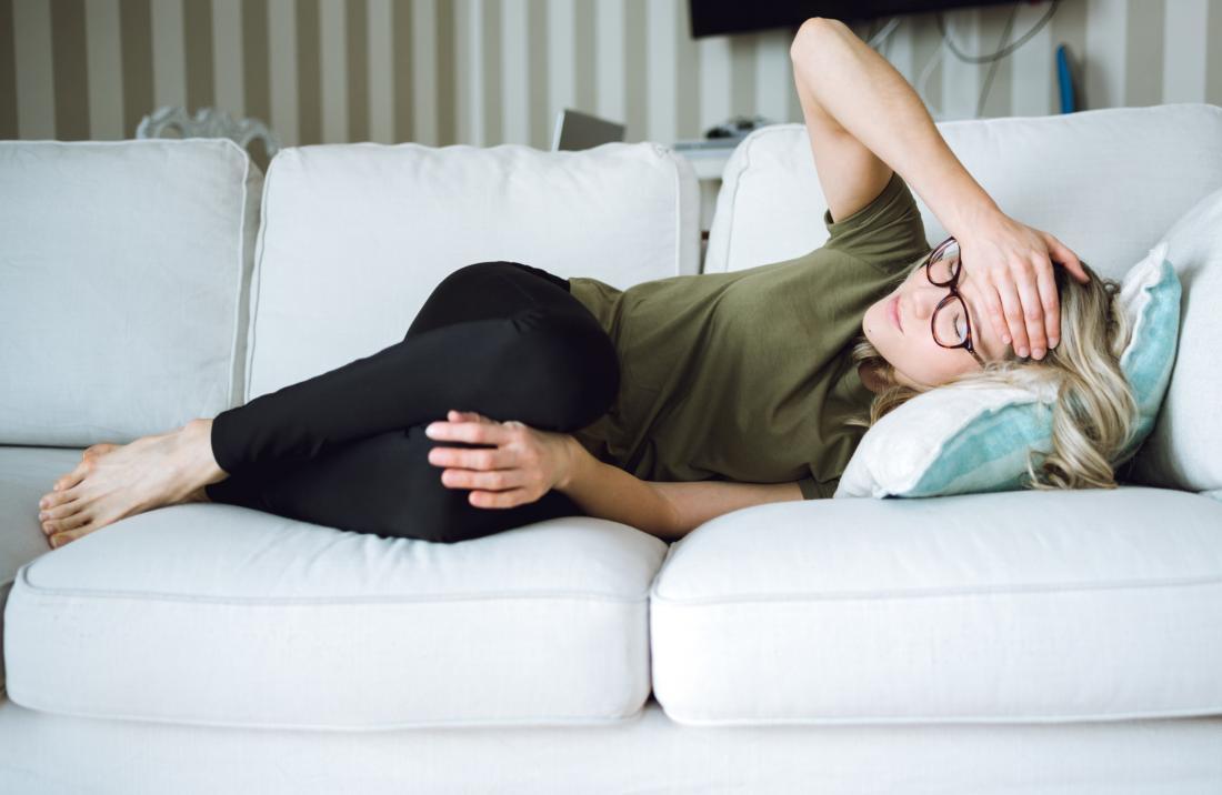 Жена лежаща от едната си страна на дивана с главоболие мигрена.