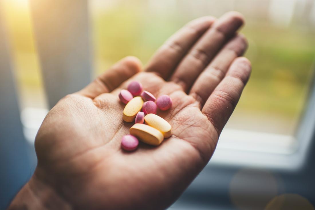 Лице, което държи няколко хапчета за медикаменти и допълва витамини в дланта на ръката.