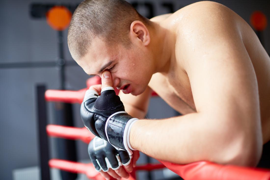 Боксьор или боец, облегнат на пръстена, държащ мост на носа поради нараняване, причиняващо главоболие.
