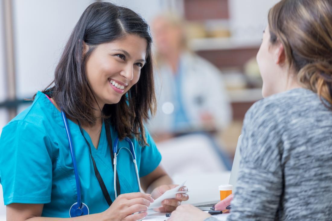 Ärztin scheuert innen sich, Verordnung mit Patienten besprechend.