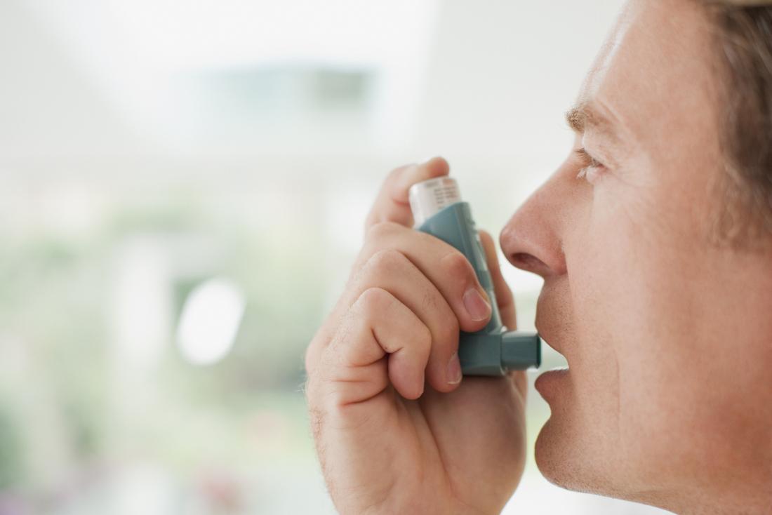 Feche acima do homem que põe o inalador para mouth para tratar o ataque da asma.