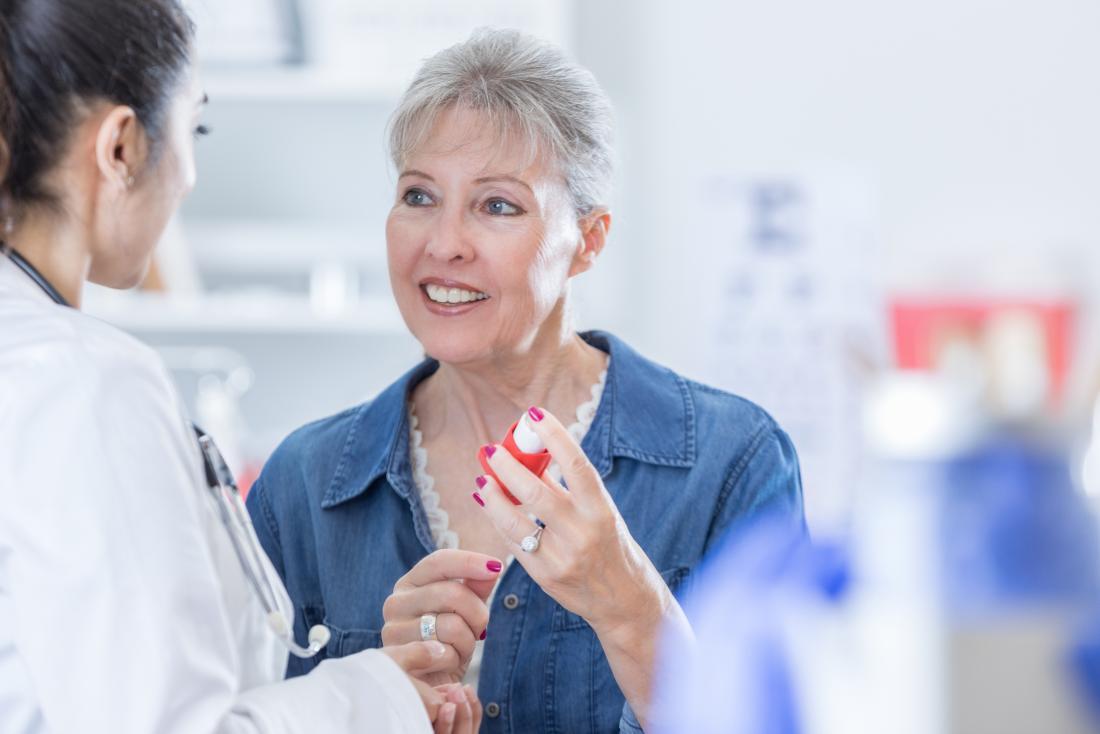 Médico, aconselhando o paciente sobre o inalador.