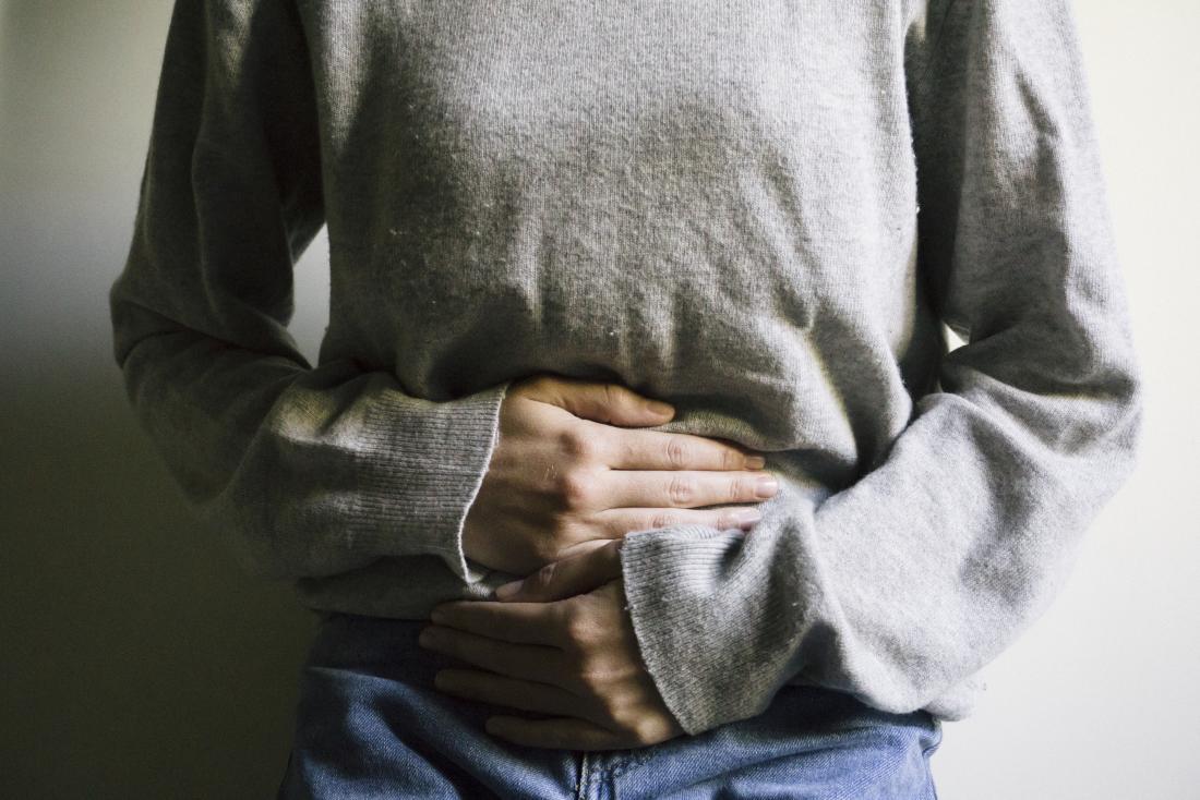 Frau, die ihren Magen möglicherweise wegen der Implantationsverkrampfung hält