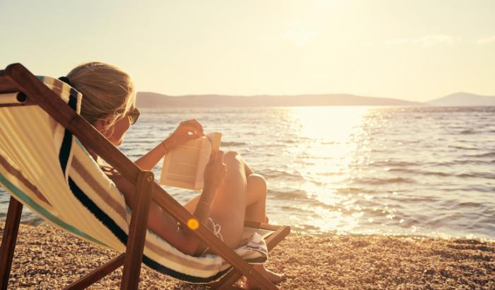 太陽の下でビーチで読書する女性