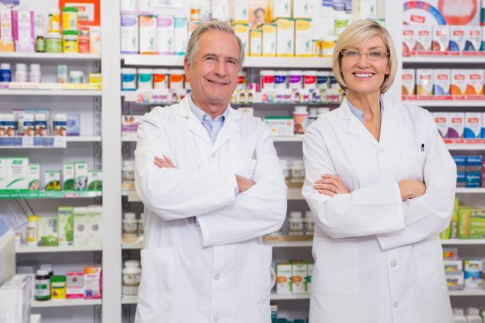 Due farmacisti in piedi di fronte a scaffali di medicina.