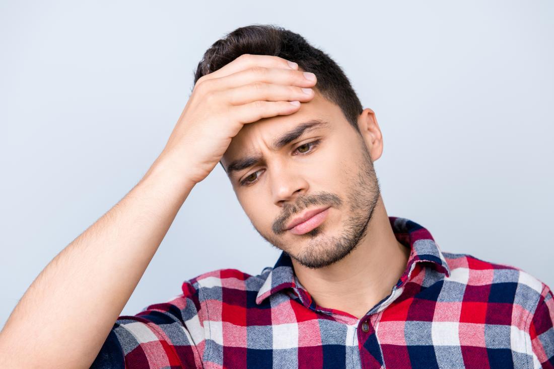 Mann mit Kopfschmerzen oben auf den Kopf, der Stirn in den Schmerz hält.