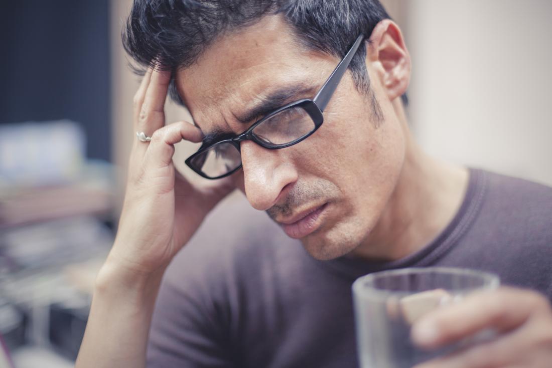 Homme avec maux de tête sur le côté droit de la tête tenant la tête et tenant le verre.