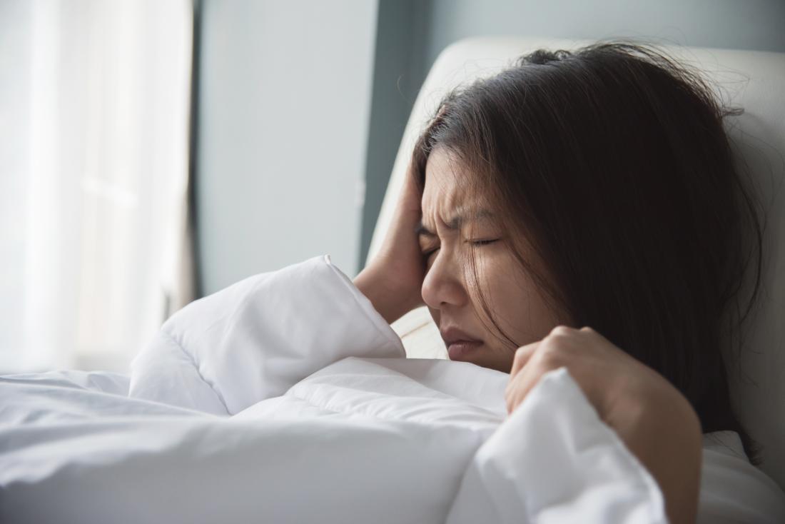 Femme avec la migraine dans le lit tenant le côté droit de la tête.