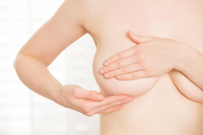 donna controlla il seno per eventuali segni di cancro al seno