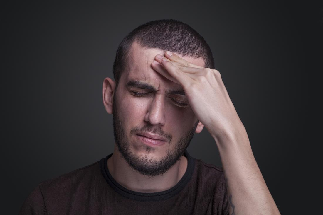 Mann hält den Kopf in Schmerzen
