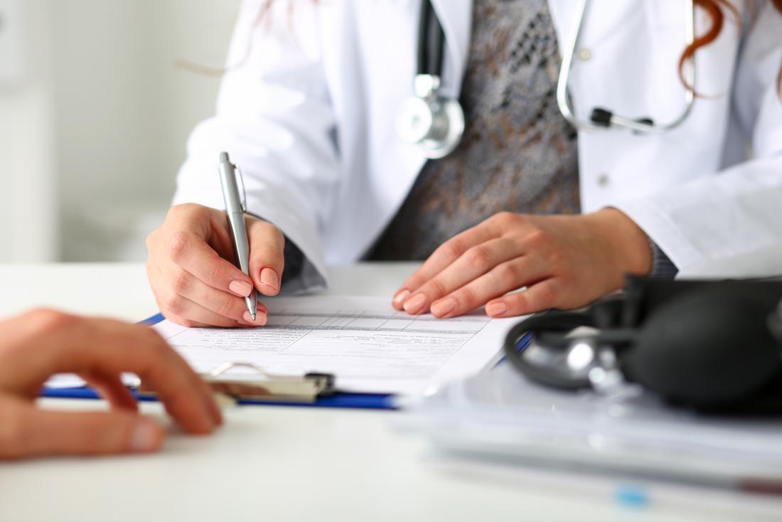 Perca das mãos dos doutores que escrevem na prancheta com o paciente no primeiro plano.