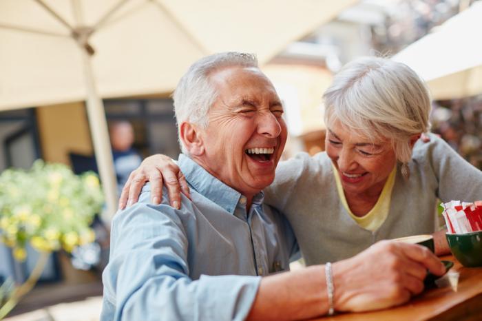 Ein älterer Mann und eine ältere Frau genießen ein Lachen bei einer Tasse Kaffee