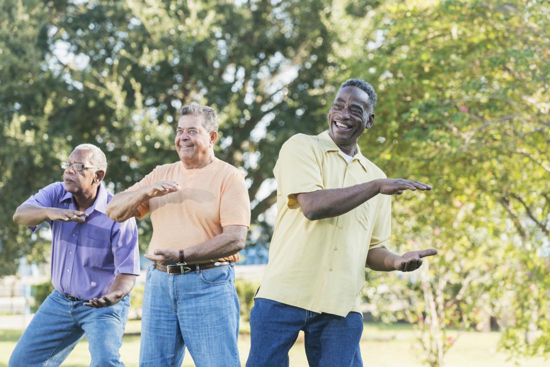 трима старши мъже, които правят тай чи на открито.