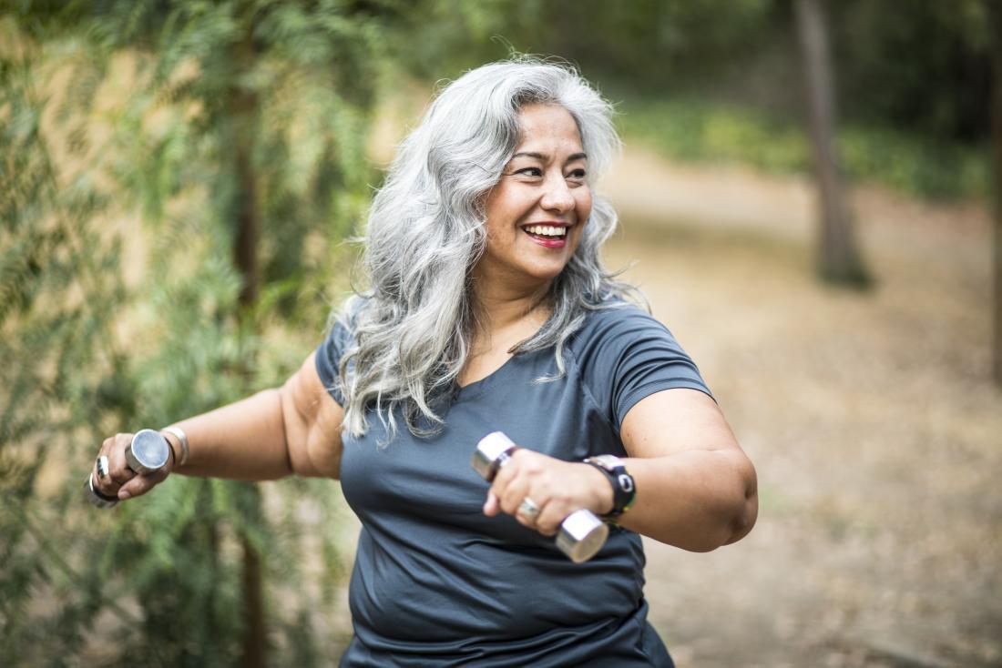 Старши жена на открито упражнява с тежести гири.