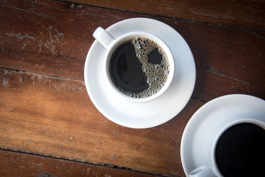 cà phê đen trong hai ly trên bàn gỗ.
