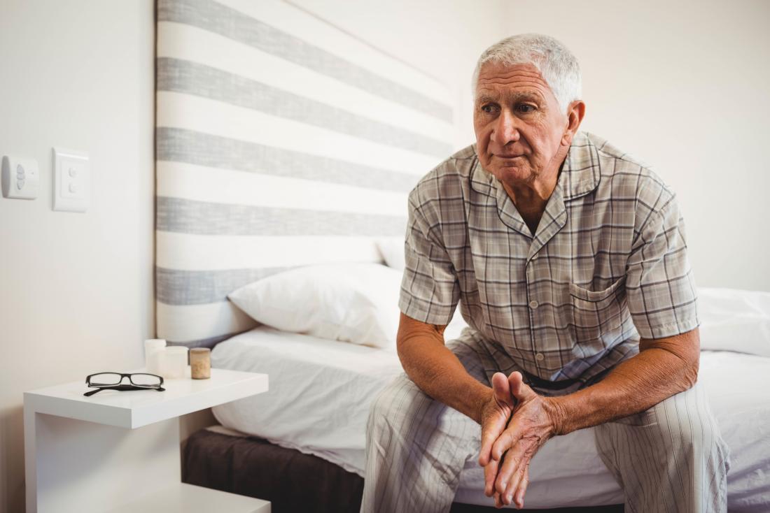 Người đàn ông lớn tuổi ngồi trên mép giường.