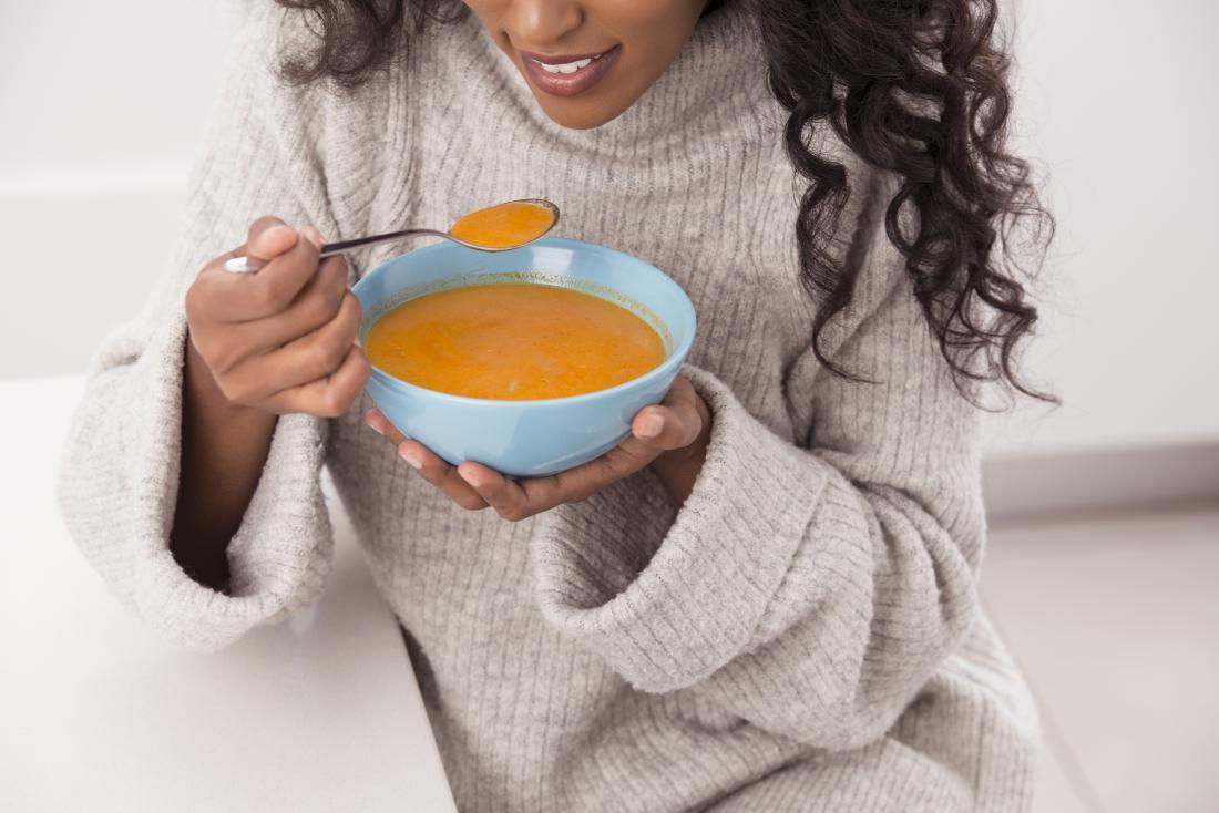 Người phụ nữ đang ăn thức ăn sau khi đã lấy được những chiếc răng khổng lồ, ngồi với tô súp rau.