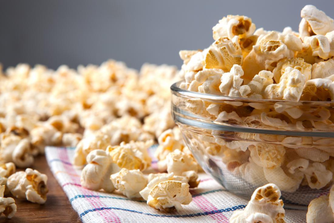 Popcorn chất đống trong một cái bát và nằm rải rác trên bàn.