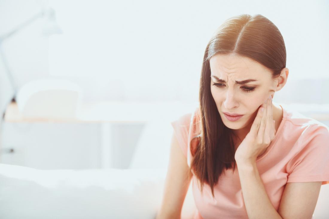 Người phụ nữ với đau răng khôn ngoan cầm bên miệng trong đau đớn.