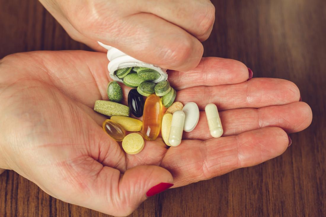 Suppléments de vitamines et de minéraux étant versé dans la paume des personnes.