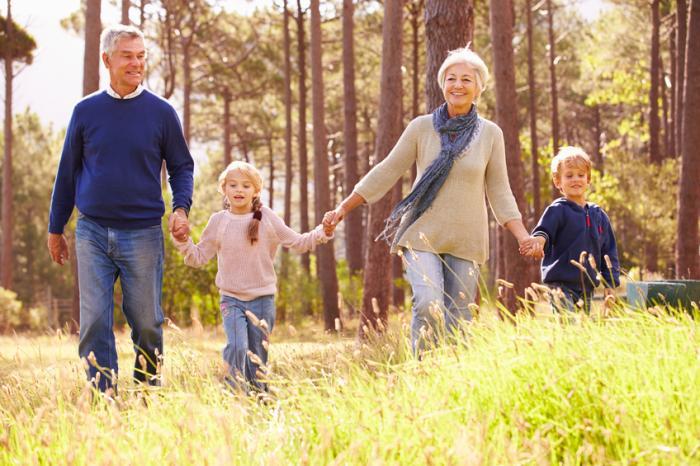 Les enfants et les grands-parents marchent ensemble dans les bois