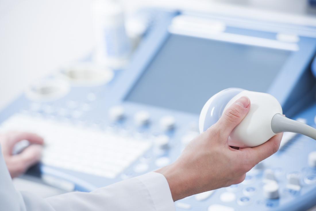 Techniker, der Ultraschallscanner an der Maschine hält, um Hodenultraschall durchzuführen.