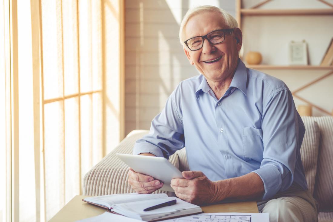 Heureux homme senior regardant la tablette