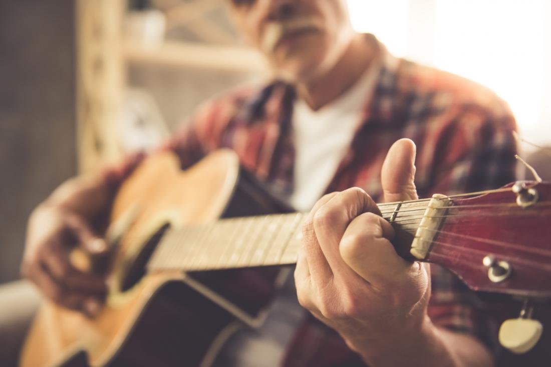 homem sênior tocando uma guitarra