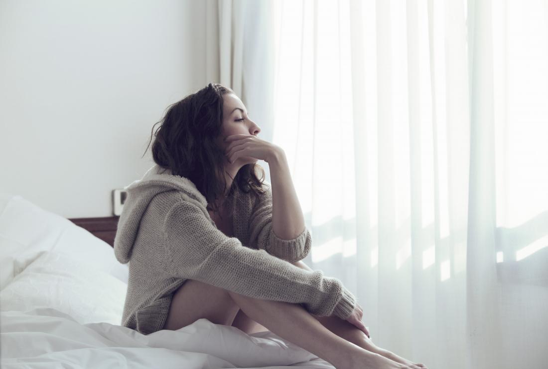 Femme déprimée assise sur le lit.