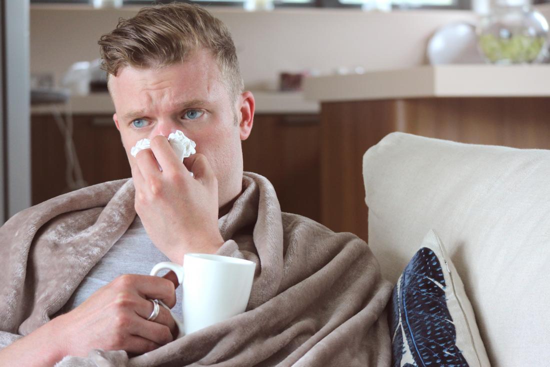 Homem com nariz ralo que bebe a bebida quente em casa sob a cobertura no sofá.