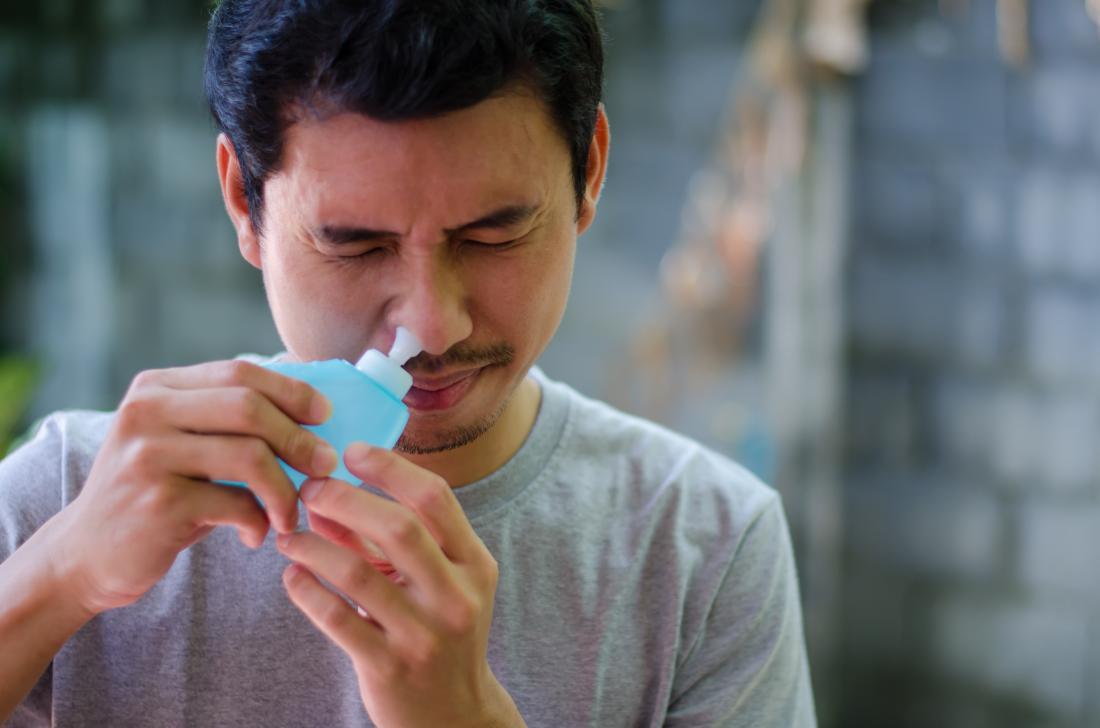 Homme en utilisant neti pot pour soulager la pression des sinus.