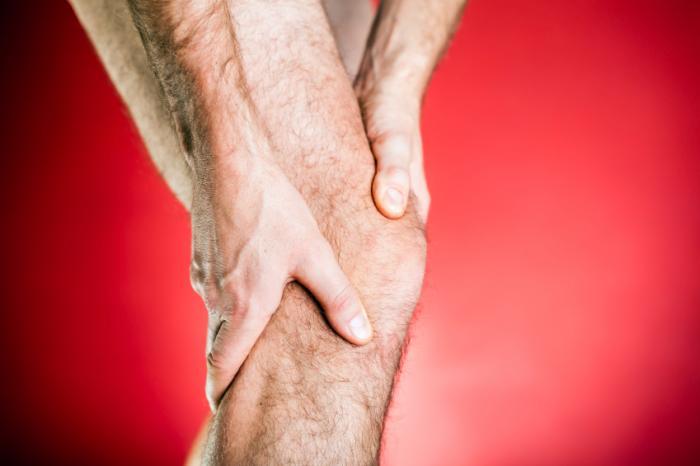 [L'uomo tiene il ginocchio nel dolore]